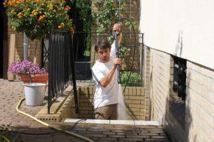 Mann mit Hochdruckreiniger reinigt Treppe